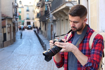 Man looking at the screen of his professional camera during a trip