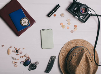 Travel concept, documents, hat, compass, money, phone and camera on a wooden background