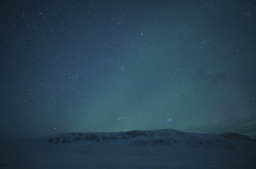Mountain against starry sky during winter