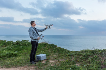 Man pilot, holds the drone before the flight.