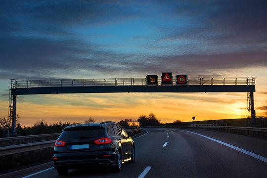 Verkehrsleitsystem Tempo 80 auf Autobahn A6 Baustellenwarnung im Sonnenuntergang