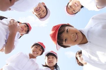 Elementary school children and teacher looking into camera, Japan