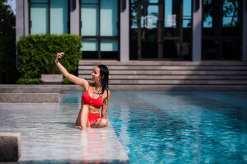 people, technology, travel, tourism and summer concept - happy young woman in bikini swimsuit and sunglasses taking selfie with smatphone over swimming pool on beach with palm trees background