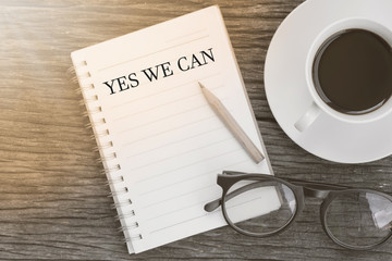 Concept YES WE CAN on notebook with glasses, pencil and coffee cup on wooden table.
