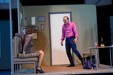Two actors, brunette woman in a brown dress and a man in a pink shirt and blue suit, playing the role on stage