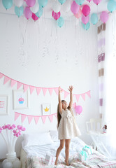 Cute girl playing with balloons in room decorated for birthday party
