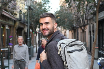 Happy young male heading to the university in Europe