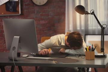 Tired designer sleeping in office