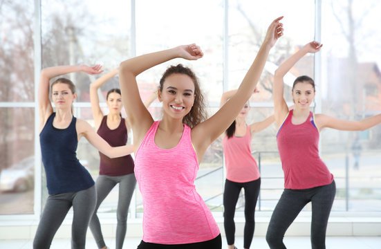 Young sporty women training in dance hall