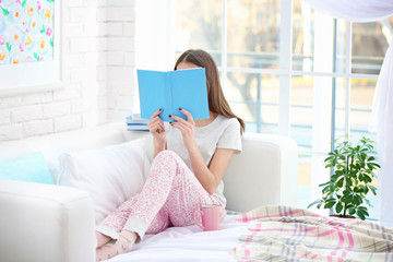 Young beautiful woman reading book at home