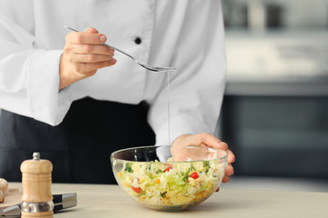 Female chef adding oil to vegetable salad in glass bowl closeup