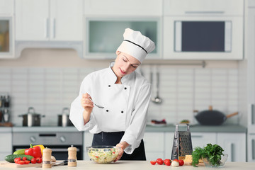 Female chef adding oil to vegetable salad in kitchen