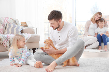 Father with his daughter and cat at home