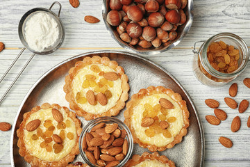 Metal tray with delicious crispy tarts on wooden background