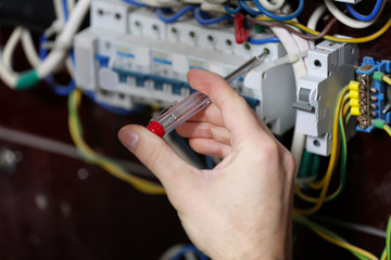 Hand of electrician at work, closeup