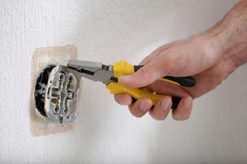 Hands of electrician installing socket, closeup