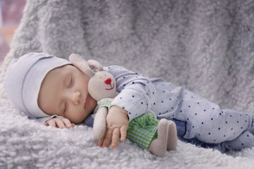 Cute little baby with bunny toy sleeping on plaid at home