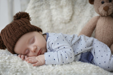 Cute little baby sleeping on plaid at home