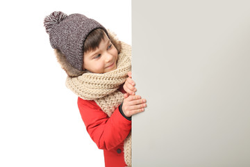 Cute little boy in warm clothes with poster on white background