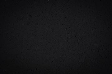 Schwarze poröse Steinwand als strukturierter Hintergrund