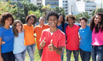 Young latin american man with braces with large group of international friends