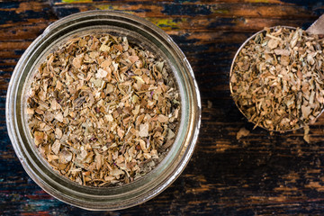 Dried basil in spice jar with measuring spoon