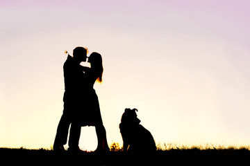 Silhouette of Loving Young Couple Hugging at Sunset Outside