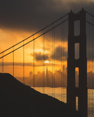 View of Golden Gate Bridge with city in background during sunset