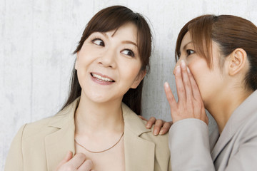 Buisnesswoman Whispering to Colleague