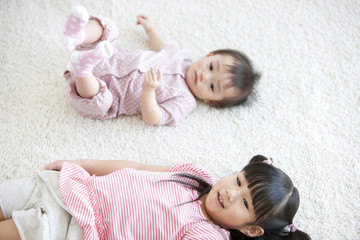 Baby girl and girl lying down on carpet