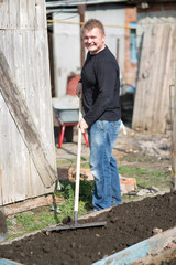 A man runs a rake on the ground