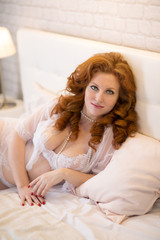 seductive woman with red hair lies on a bed