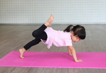 cute toddler girl practicing yoga