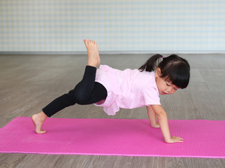 Cute toddler girl practicing yoga and doing exercise