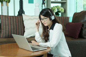 Business Asian girl using a laptop and listening to music, person