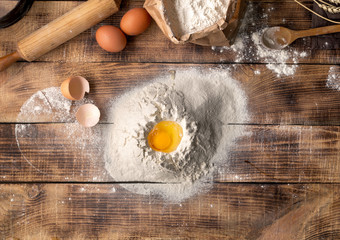 Wall Mural - Egg yolk in flour on a wooden background