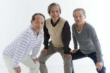 Three Cheerful Senior Men Crouching