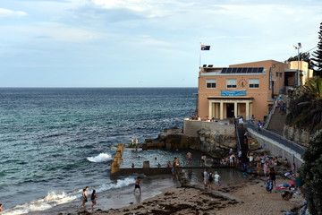 Sydney, Australia - Feb 5, 2017. Coogee Surf Life Saving Club and swimming pool with ocean view in summer time. People relaxing, swimming and sun bathing on Coogee beach.