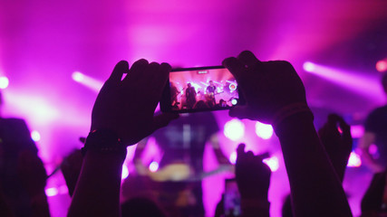 Fans womans hands recording video with smart phones at rock concert on pink colors