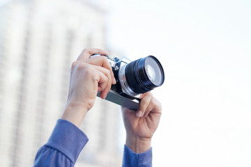 woman holding film camera taking photo in the city