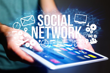 Concept of man holding futuristic interface with social network  title and multimedia icons flying all around - Internet concept