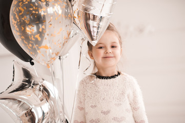 f78fb4e467f6 Smiling baby girl 5-6 year old wearing stylish black dress holding ...