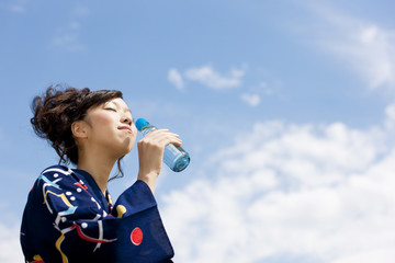 Young woman in Yukata drinking soda