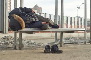 Drunk beggar sleeping on bus stop