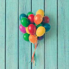 Colorful bunch of Easter egg balloons on blue wooden background. Minimal creative concept. Flat lay.