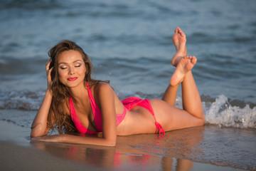 Beautiful young woman in a pink bikini sits on a beach. Horizontal shot.