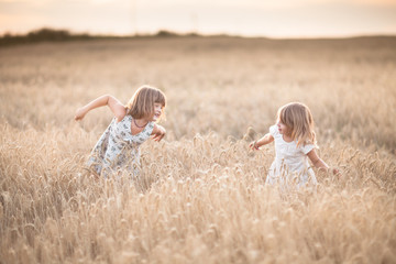 Two emotional sisters girls dance at sunset