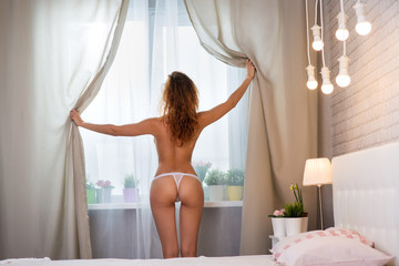 red-haired girl in lingerie in the interior of the bedroom