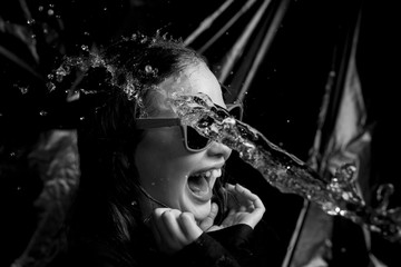 water throwing to a young girl in hands and face with black background