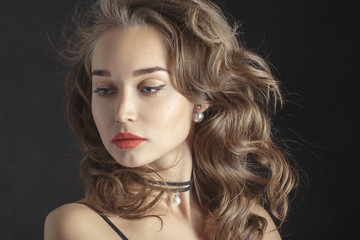 luxury woman with curly long hair on black background